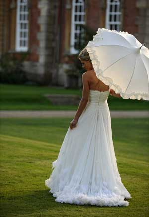 Bride with parasol on the front lawn